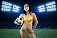 Sexy het voetbalbal van de vrouwenholding bij gebied Royalty-vrije Stock Foto's