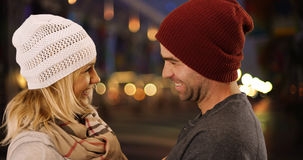 Hipster couple laughing and talking together outdoors at night.  royalty free stock photography