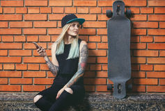 Sexy hipster girl in tattoo against a red brick wall with a long board. Stock Images