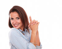 Sexy hispanic lady pointing up and smiling at you Stock Photo