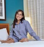 Hispanic woman laying in bed men's shirt Stock Photos