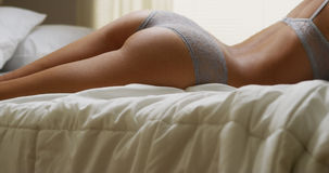 Sexy hispanic woman lying on bed in lingerie Royalty Free Stock Image