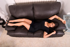 Sexy hispanic woman on sofa. Sexy Hispanic woman in a  short black dress laying on her back on a black leather sofa in a stylish modern living room. Shot taken Royalty Free Stock Photos
