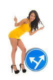 Sexy hitchhiking girl. Sexy girl hitchhiking with traffic sign in studio Royalty Free Stock Photography