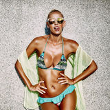 Hot tanned young woman in sunglasses and swimsuit showing t. Ongue and having fun royalty free stock images