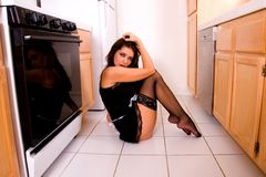 Sexy house wife. Wife angle shot of a sexy house wife wearing lace top hold-ups, sitting on the kitchen floor Stock Image