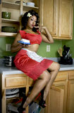 Sexy house wife. Attractive African American eating cake off her finger, sitting on kitchen counter Stock Photos