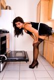 Sexy house wife by oven. Stock Photography