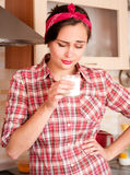 Sexy housewife dislike milk. Sexy housewife in kerchief dislike milk standing on the kitchen Royalty Free Stock Photos