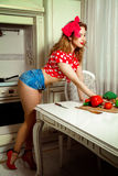 Sexy housewife in pinup style posing in the kintchen Stock Photo