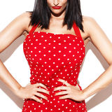 Sexy housewife in red dotted apron closeup. Sexy housewife in red dotted apron posing at white wall Royalty Free Stock Images