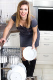 Sexy housewife takes out the plates from the dishwasher Stock Images