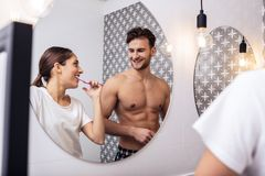 Sexy husband with nice abs standing near his wife in the bathroom. Sexy husband. Sexy dark-haired handsome husband with nice abs standing near his wife in the stock photography