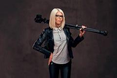 Sexy intelligenter blonder weiblicher Fotograf hält eine Berufskamera mit einem Stativ und wirft an einem Studio auf Lizenzfreies Stockbild