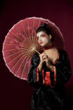 Sexy japanese geisha looking sideways. Sexy geisha in studio with a red painted umbrella Stock Image
