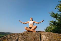 jonge atletische vrouw met spierlichaam het praktizeren yoga op de rots Blauwe hemelachtergrond Ogenblik van harmonie en Stock Fotografie