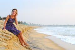 Sexy jonge blonde meisjeszitting op strand stock foto's
