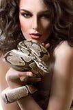 Sexy jonge donkere ingehuurde vrouw die topless holding stellen een slang Royalty-vrije Stock Afbeeldingen