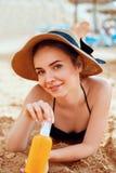Sexy Jonge Vrouw in de Flessen van de Bikiniholding van Zonnescherm in Haar Handen Skincare Een Wijfje die de Room van de Zonroom royalty-vrije stock afbeelding