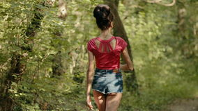 Sexy jonge vrouw die door het hout lopen stock footage