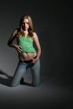 Sexy jonge vrouw die haar strak groen overhemd opheft stock afbeelding