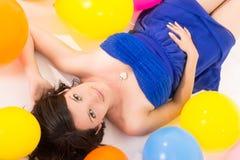 Sexy jonge vrouw die op vloer onder ballons liggen stock foto's
