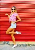 Sexy jonge vrouw in jeansborrels, overhemd en zonnebril die ou stellen Stock Afbeeldingen