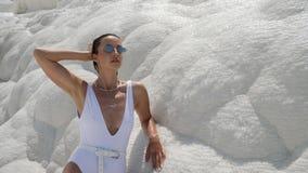 Sexy jonge vrouw in wit zwempak die zich op een witte berg bevinden stock video