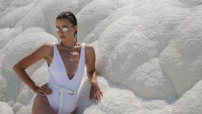 Sexy jonge vrouw in wit zwempak die zich op een witte berg bevinden stock videobeelden