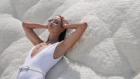 Sexy jonge vrouw in wit zwempak die zich op een witte berg bevinden stock footage