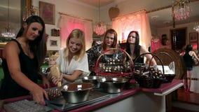 Sexy jonge vrouwen die chocoladepralines maken stock video
