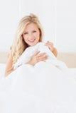 Sexy junge blonde Bedeckung selbst mit Daunendecke Stockbild