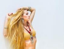 Sexy junge blonde moderne Frau in einem goldenen Bikini Stockbild