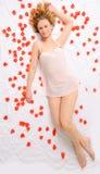 Sexy junge Frau auf Bett mit den roten Blumenblättern Lizenzfreie Stockfotos