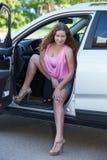 Sexy junge Frau in den hohen Absätzen und ein rosa T-Shirt, das im Auto sitzt Lizenzfreie Stockfotos