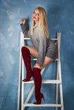 Sexy junge Frau in den roten Stiefeln sitzt auf der Treppe Schönes Mädchen in einer grauen gemütlichen Strickjacke Lizenzfreie Stockfotos