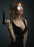 Sexy junge Frau in der Spiegelsonnenbrille, die Gewehratelieraufnahme hält Stockfotos
