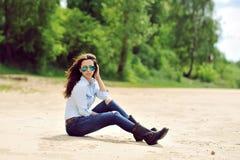 Sexy junge Frau, die auf einem Modeporträt des Strandes im Freien sitzt Lizenzfreies Stockbild