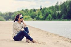 Sexy junge Frau, die auf einem Modeporträt des Strandes im Freien sitzt Stockfotos