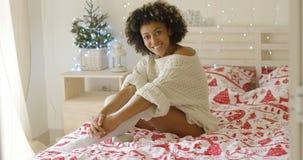 Sexy junge Frau, die auf ihrem Bett am Weihnachten sich entspannt Lizenzfreies Stockfoto