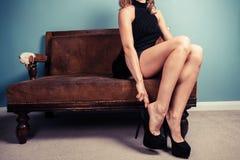 Sexy junge Frau, die auf Schuhe sich setzt Stockfotos