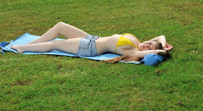 Sexy junge Frau, die in der Bikinispitze und -kurzschlüssen ausbreitet Lizenzfreie Stockfotografie