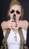 Sexy junge Frau, die in der Militäruniform WW2 und in einer Waffe aufwirft Lizenzfreies Stockfoto