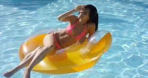 Sexy junge Frau, die in einem Swimmingpool ein Sonnenbad nimmt lizenzfreie stockfotos
