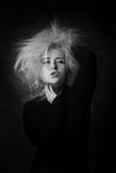 Sexy junge Frau, die Hände in ihr ungepflegtes Haar einsetzt lizenzfreie stockfotografie