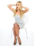 Sexy junge Frau, die ihren Kopf hält und in der Frustration schreit Stockfotografie