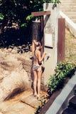Sexy junge Frau in einem Badeanzug, der eine Dusche nimmt, nachdem herein schwimmen Stockbild