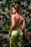 Sexy junge Frau im herrlichen grünen Kleid auf einem Blumenhintergrund Würdevolle Rückseiten- und Hüftenlinien Vertikales Foto Fa stockfotografie