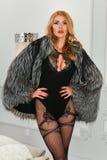 Sexy junge Frau mit dem hellen Zaubermake-up, das einen sinnlichen Wäschebodysuit- und -luxuspelzmantel aufwirft im Schlafzimmeri Lizenzfreie Stockfotografie