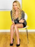 Sexy junge Geschäftsfrau, die auf Stuhl sitzt Lizenzfreies Stockbild